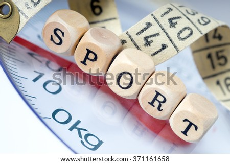 Wooden dice with the word sport and tape measure with a body scales / Sport