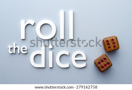 Wooden dices and roll the dice text over blue background, above view - stock photo