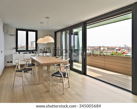 wooden dining table and chairs in the attic with a view of the city skyline, the flooring is made of natural wood - stock photo