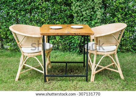 Wooden dining tables in lush garden - stock photo