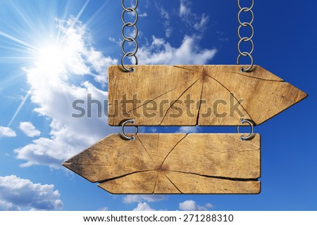 Wooden Directional Sign - Two Arrows with Chain. Wooden directional sign with two empty arrows in opposite direction hanging with metal chain on blue sky with clouds and sun rays - stock photo