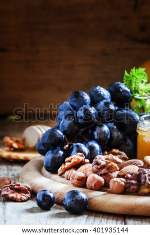 Wooden dish with appetizers to red wine, selective focus