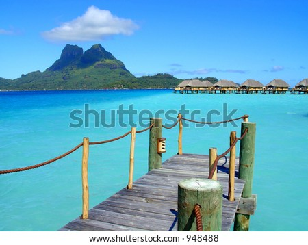 Wooden dock extending over the clear blue tropical water in Bora Bora.