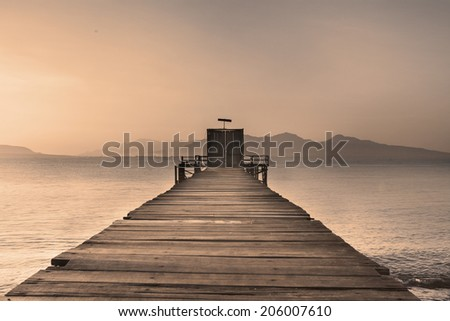 Wooden Dock on Calm Lake at Sunset - stock photo