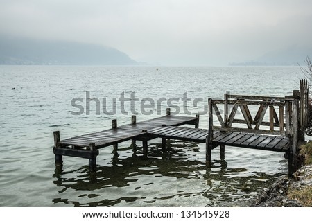 Wooden dock on the lake of Annecy, on a foggy day