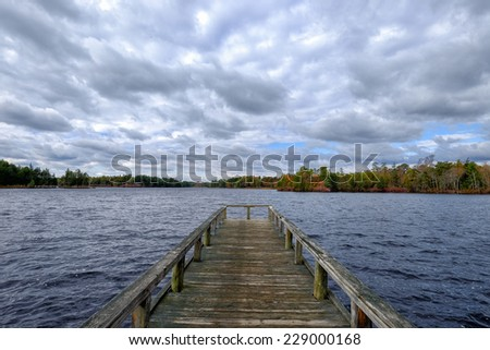 Wooden dock or pier stretching out into a lake on a dramatic cloudy day - stock photo