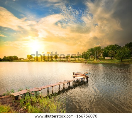Wooden dock, pier, on a lake in the evening - stock photo