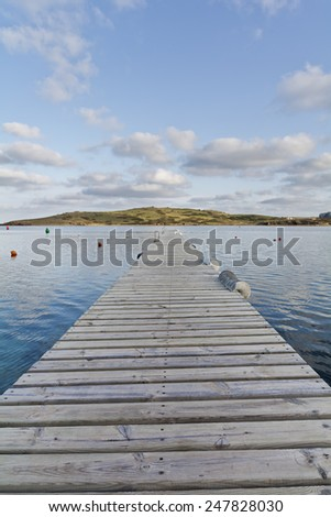 wooden dock with a blue cloudy sky behind - stock photo