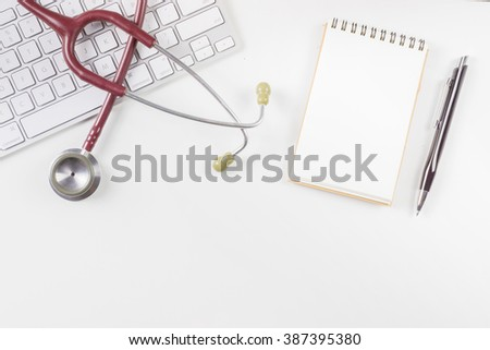 Wooden doctor desk,Doctor working,Hospital Workplace with notepad and keyboard,pen,glasses,flower pot and stethoscope,monitoring patient ,business ,healthcare and medical concept, with copy space