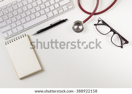 Wooden doctor desk,Doctor working,Hospital Workplace with notepad and keyboard,pen,glasses,flower pot and stethoscope,monitoring patient ,business ,healthcare and medical concept, with copy space - stock photo
