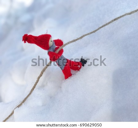 wooden doll holds onto a rope on a steep slope with snow