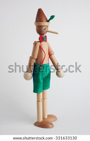 Wooden doll of Pinocchio liar with big nose on white background  - stock photo