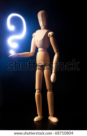 Wooden doll with a question on a hand - stock photo