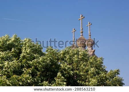 wooden dome of Temple of Saint George in Kolomenskoye out from behind the trees - stock photo