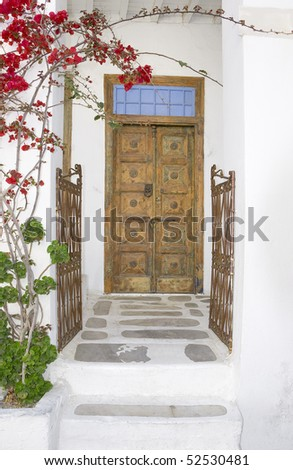 Wooden door and an old iron gate with blooming bougainvilleas