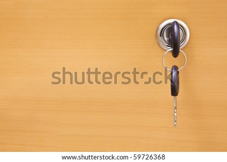 Wooden door and keys in a keyhole - stock photo