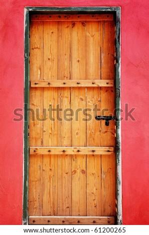 wooden door as red wall - stock photo