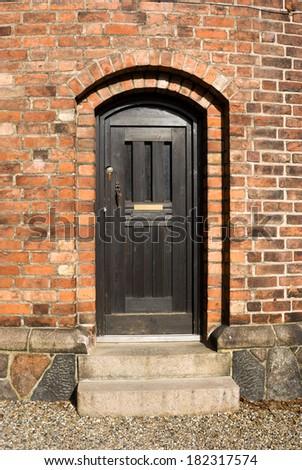 wooden door in a brick historic building  - stock photo
