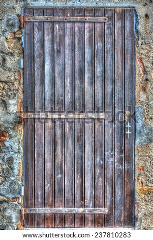 wooden door in a rustic wall. Processed for hdr tone mapping effect.