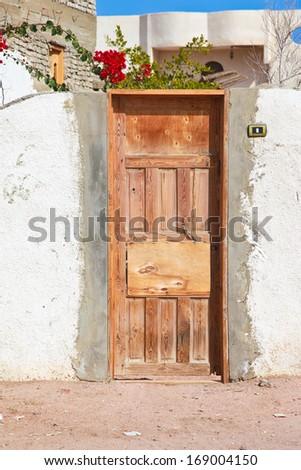 Wooden door on white wall in Dahad, Egypt - stock photo
