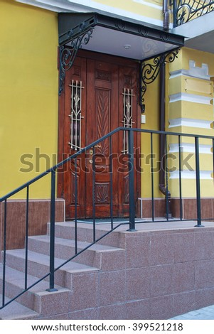 Wooden door with a canopy in a classic style. Architecture - stock photo