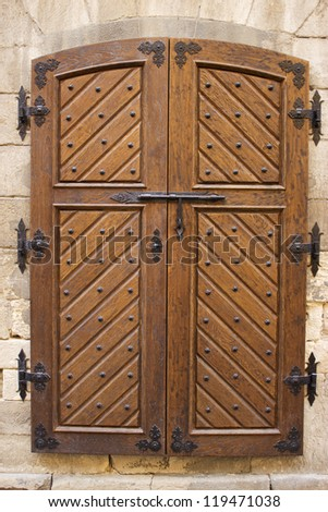 Wooden door with forged curtain - stock photo