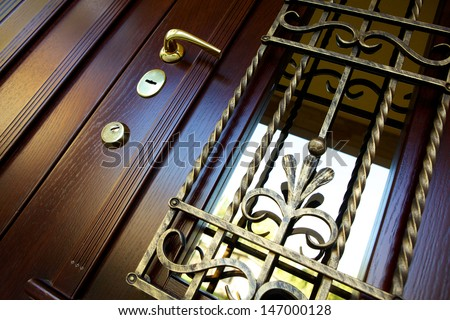 wooden door with forged metal grate  - stock photo