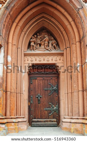 wooden doors with metal hinges and a beautiful arch