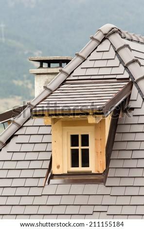 Wooden dormer on tiled roof on mountain house - stock photo