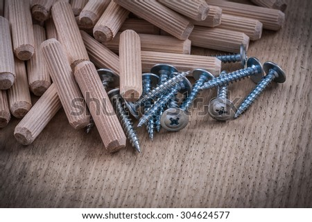 Wooden dowels and metal construction nails on wood board.