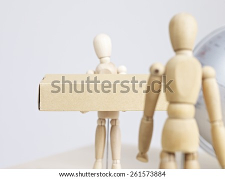 wooden dummy delivering package to another dummy with world globe in background. - stock photo