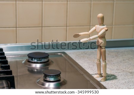 Wooden dummy, mannequin or man figurine stand near a gas burner outstretched hands. Gas turned off for non-payment. - stock photo