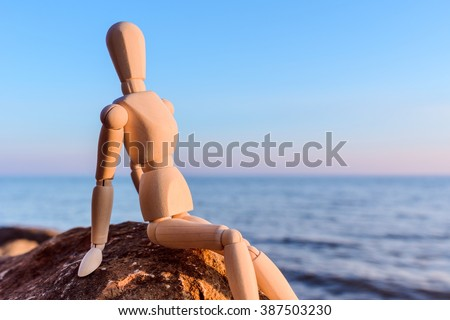 Wooden dummy sitting on the stone at the sea - stock photo