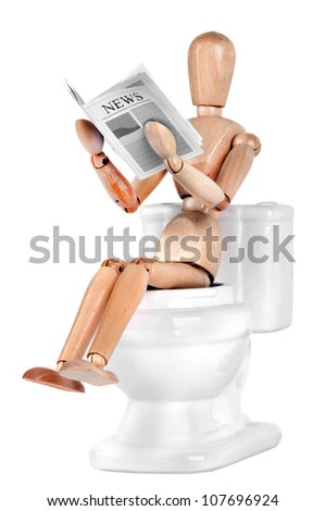 Wooden Dummy sitting on toilet and reading newspaper - stock photo