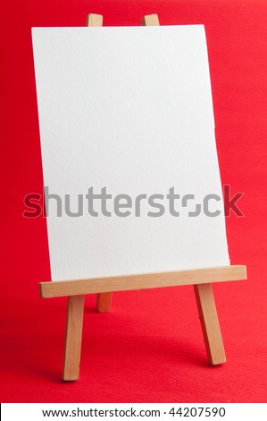 wooden easel with blank canvas on red background - stock photo