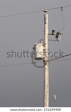 Wooden electrical pole with dark cloudy sky.