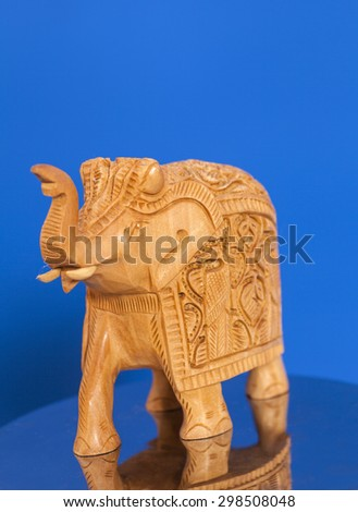 Wooden elephant sculpture on blue background - stock photo