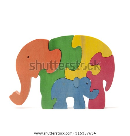 Wooden elephants puzzle on the white - stock photo