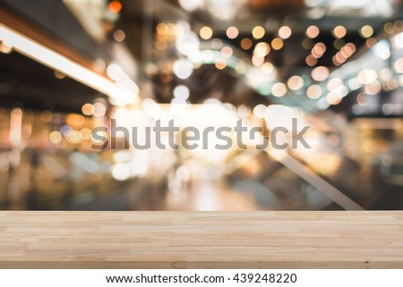 Wooden empty table top with defocus of shopping mall with bokeh light background, use for montage or product display, business concept