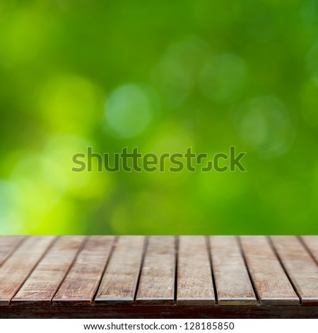 Wooden empty table with natural green background - stock photo