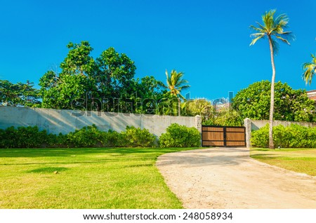 Wooden entrance of a luxury properties in exotic scenery - stock photo