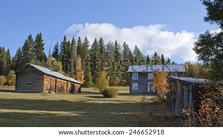 Wooden farmhouses far out in rural country. Meadows, colorful trees and afternoon sunshine. - stock photo
