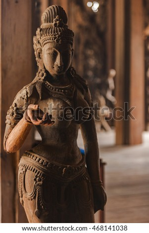 Wooden female statue in the temple built by ancient civilizations. An extraordinary artwork made of wood carved. The young woman has tired facial expression. Jewelries on the woman. Pattaya, Thailand.