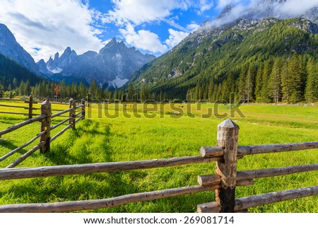 Wooden fence and green pasture in mountain valley of Fischleintal, Dolomites Mountains, South Tyrol, Italy - stock photo