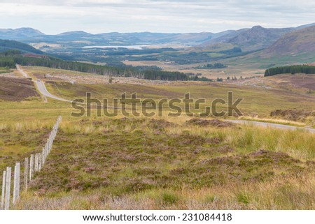 Wooden fence between hills and slopes in the Scottish Highlands near Loch Tarff - stock photo