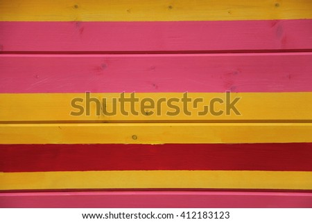 Wooden fence colored in pink, yellow and red colors
