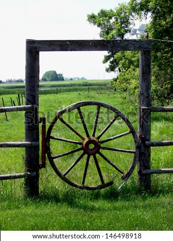 wooden fence gate with old wagon wheel - stock photo
