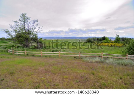 wooden fence in a park by a bay in springtime - stock photo