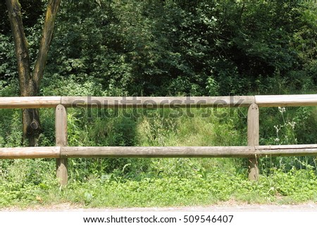 Wooden fence of a ranch on a tree background