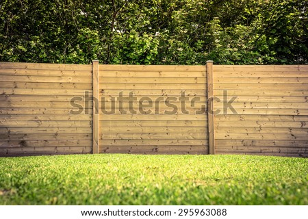 Wooden fence on a green lawn - stock photo